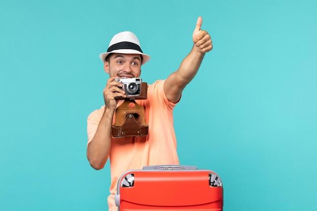 Mężczyzna na wakacjach ze swoją czerwoną walizką robi zdjęcia aparatem na niebiesko