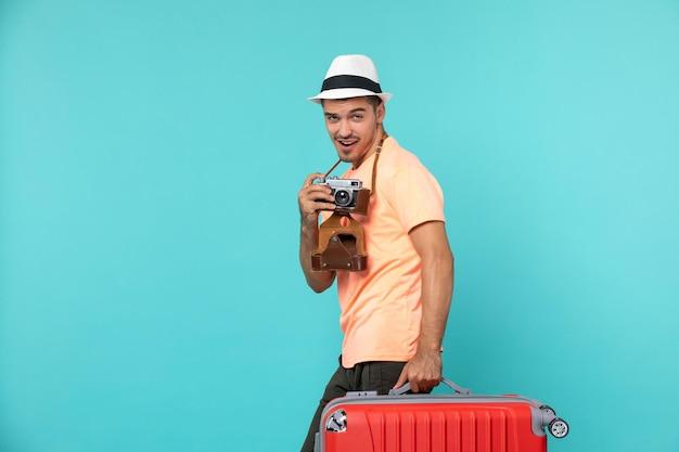 Mężczyzna na wakacjach ze swoją dużą czerwoną walizką i aparatem robiącym zdjęcia na niebiesko