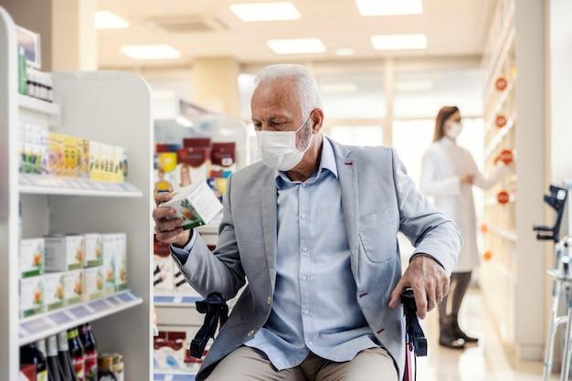 Mężczyzna na wózku inwalidzkim chodzi po półkach z lekami w aptece.