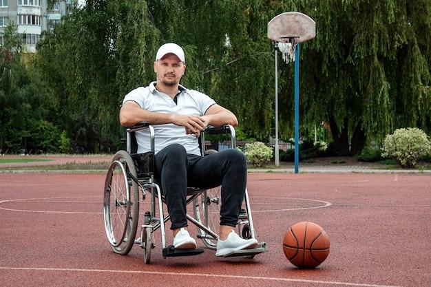 Mężczyzna na wózku inwalidzkim gra w koszykówkę na boisku sportowym. pojęcie osoby niepełnosprawnej, spełnionego życia, osoby z niepełnosprawnością, sprawności, aktywności, pogody ducha.