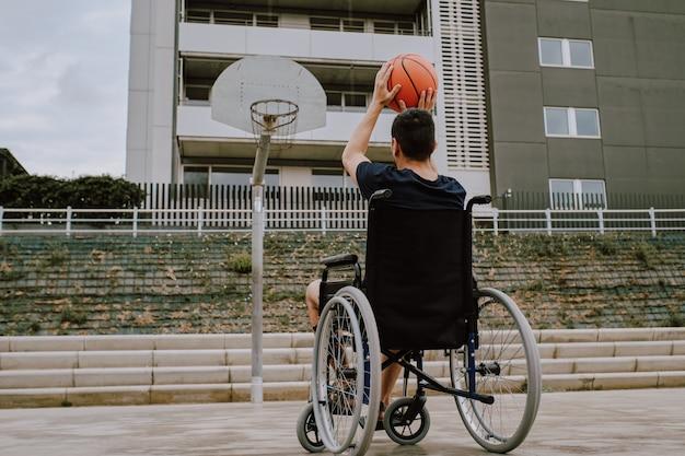Mężczyzna na wózku inwalidzkim gra w koszykówkę