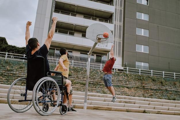 Mężczyzna na wózku inwalidzkim gra z przyjaciółmi w koszu