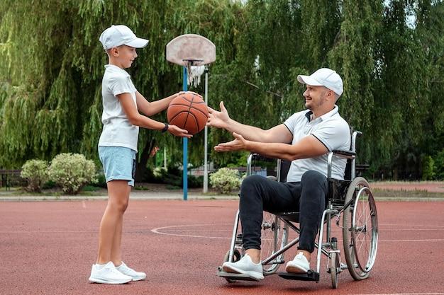 Mężczyzna na wózku inwalidzkim gra z synem w koszykówkę na boisku sportowym. niepełnosprawny rodzic, szczęśliwe dzieciństwo, koncepcja osoby niepełnosprawnej.