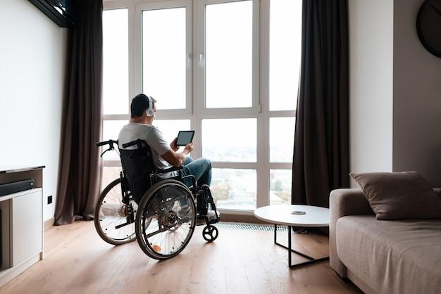Mężczyzna na wózku inwalidzkim ma słuchawki na głowie