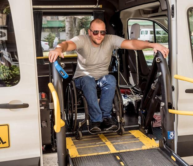 Mężczyzna na wózku inwalidzkim na podnośniku pojazdu dla osób niepełnosprawnych.