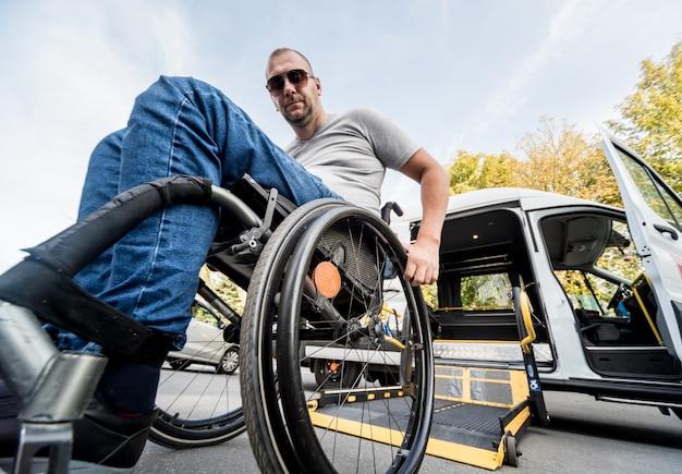 Mężczyzna na wózku inwalidzkim na podnośniku specjalistycznego pojazdu dla osób niepełnosprawnych.