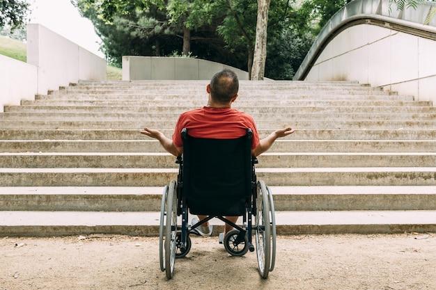 Mężczyzna na wózku inwalidzkim oburzony przed schodami
