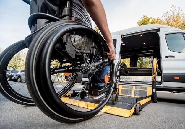 Mężczyzna na wózku inwalidzkim podjeżdża do windy specjalistycznego pojazdu
