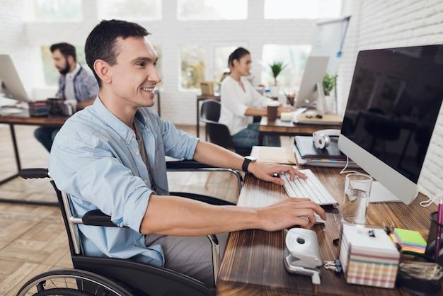 Mężczyzna na wózku inwalidzkim pracuje na komputerze w biurze.