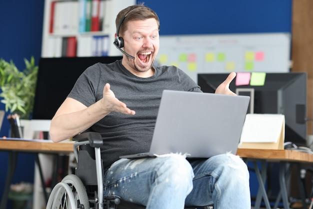 Mężczyzna na wózku inwalidzkim w zestawie słuchawkowym komunikuje się za pośrednictwem laptopa. praca dla niepełnosprawnych koncepcja