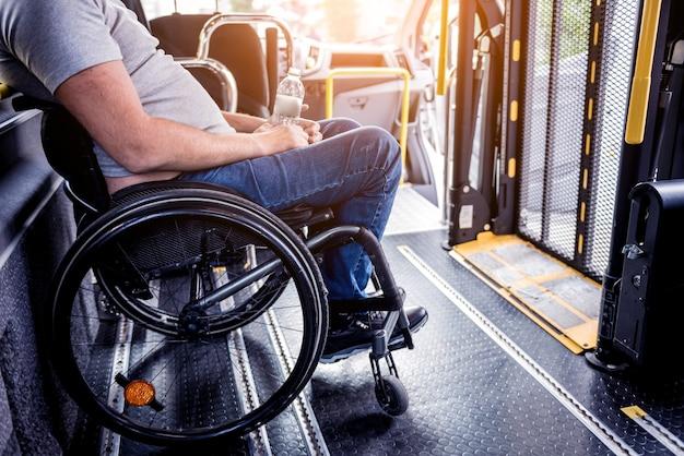 Mężczyzna na wózku inwalidzkim wewnątrz specjalistycznego pojazdu z windą dla osób niepełnosprawnych.