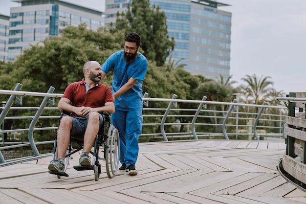 Mężczyzna na wózku inwalidzkim z jego asystentem na zewnątrz