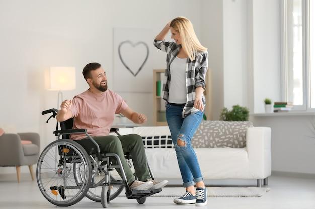 Mężczyzna na wózku inwalidzkim z piękną kobietą tańczącą w domu