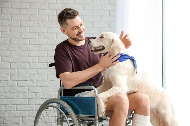 Mężczyzna na wózku inwalidzkim z psem-przewodnikiem w pomieszczeniu