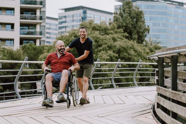 Mężczyzna na wózku inwalidzkim ze swoim asystentem na zewnątrz