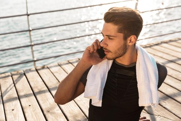 Mężczyzna na zewnątrz na plaży siedzący, rozmawiając przez smartfona