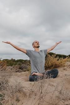Mężczyzna na zewnątrz robi joga