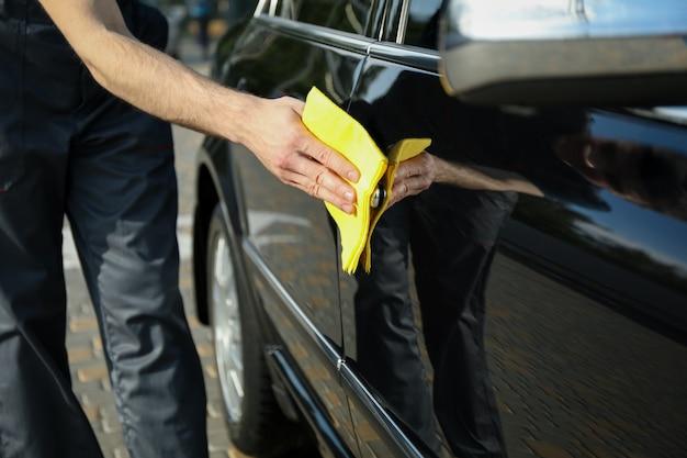 Mężczyzna naciera samochód. myjnia samochodowa.