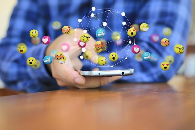 Mężczyzna naciskający na telefon komórkowy z siecią emotikonów unoszącą się powyżej