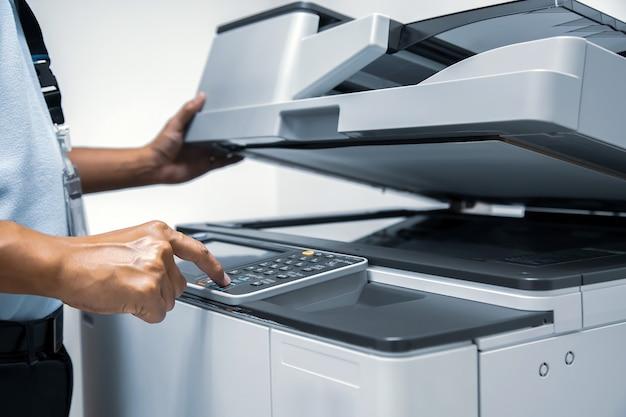 Mężczyzna naciśnij przycisk start na kopiarce, aby użyć kserokopiarki.