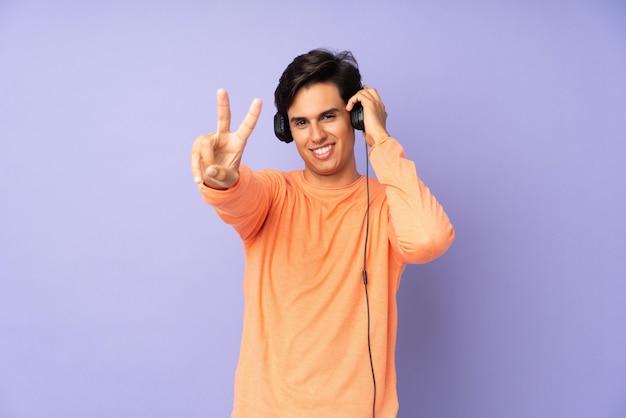 Mężczyzna nad purpurową ścianą słucha muzyki i śpiewa