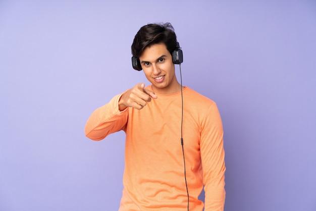 Mężczyzna nad purpurową ścianą słucha muzyki i wskazuje na przód