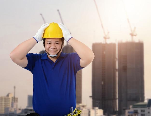 Mężczyzna nadzorca budowlany lub pracownik z wyposażeniem ochronnym
