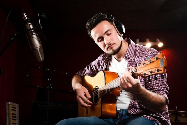 Mężczyzna nagrywa gitarę akustyczną i jest ubranym słuchawki
