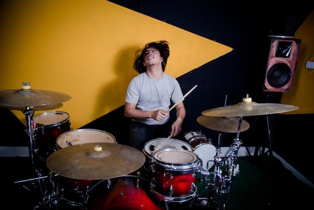 Mężczyzna nagrywa muzykę na bębnie ustawionym w studiu