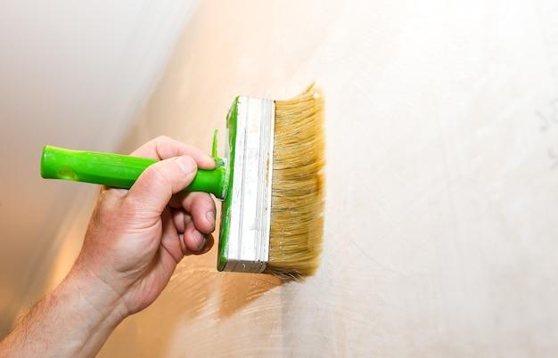 Mężczyzna nakłada klej na ścianę za pomocą pędzla. wiszące tapety. prace remontowo-remontowe remontowe w mieszkaniu. renowacja w pomieszczeniu.