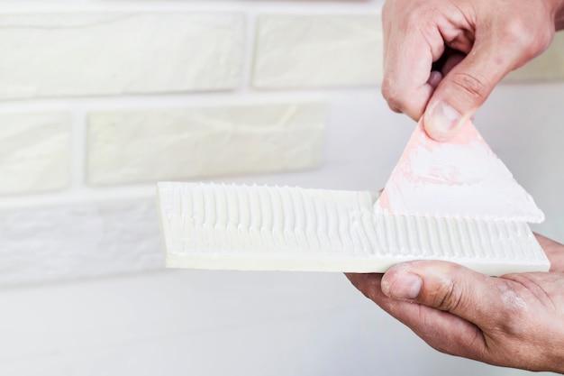 Mężczyzna nakłada klej na tynk z białych płytek, aby przykleić go do ściany