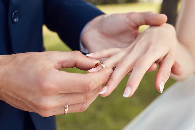 Mężczyzna nakłada obrączkę na palec panny młodej