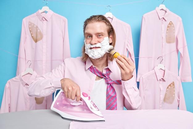 Mężczyzna nakłada pieniący się żel do golenia wygląda na zadowolonego zajęty prasowaniem używa żelazka parowego przygotowuje się do daty stoi przy desce na niebiesko