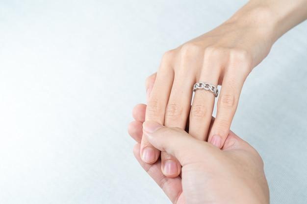 Mężczyzna nakłada pierścionek z brylantem na ręce kobiety na białym