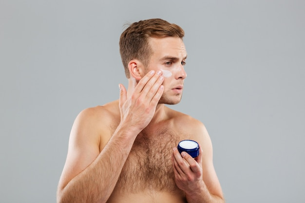 Mężczyzna nakładający kremowy balsam na twarz odizolowaną na szarej ścianie