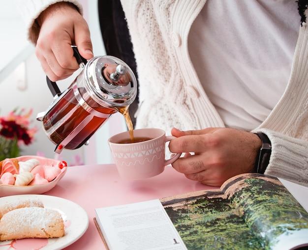 Mężczyzna nalewa czarną herbatę w filiżankę od francuza ekspresowego