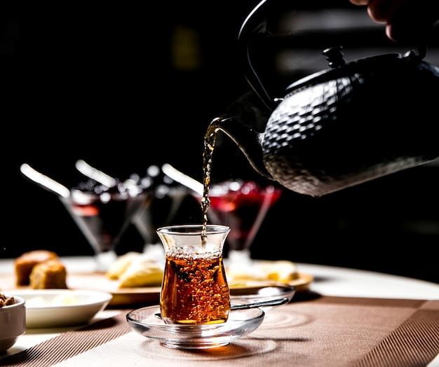 Mężczyzna nalewa czarnej herbaty w zbrojnym krajowym szklanym bocznym widoku