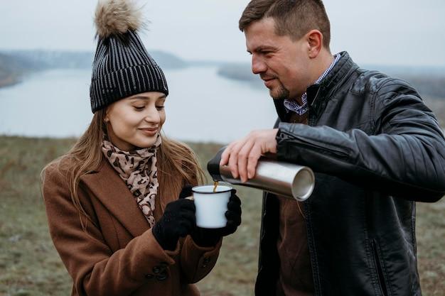 Mężczyzna nalewa gorący napój w filiżance kobiety na zewnątrz