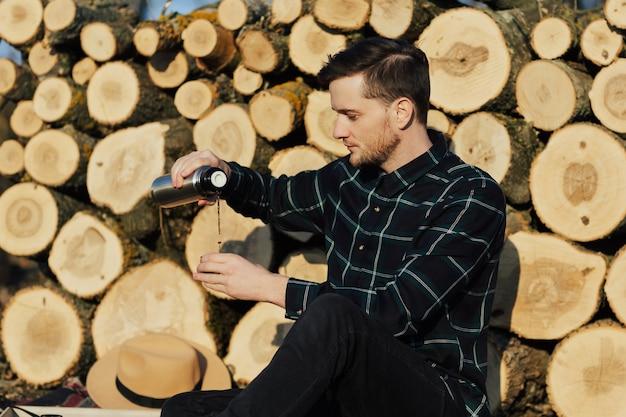 Mężczyzna nalewa gorący napój w kubek z termosu w lesie