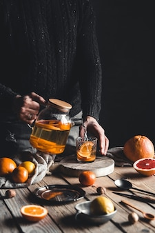 Mężczyzna nalewa herbatę cytrusową na drewniany stół. zdrowy napój w stylu vintage. wegańskie, ekologiczne produkty.