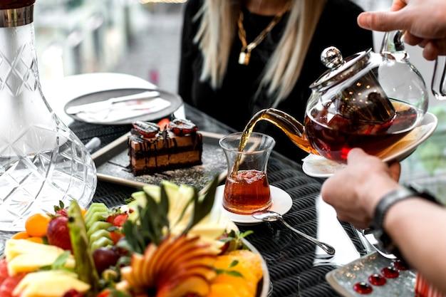 Mężczyzna nalewa herbatę do szklanki armudu