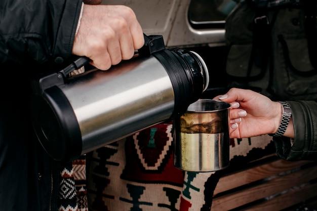 Mężczyzna nalewa kawę dla swojej dziewczyny z bliska