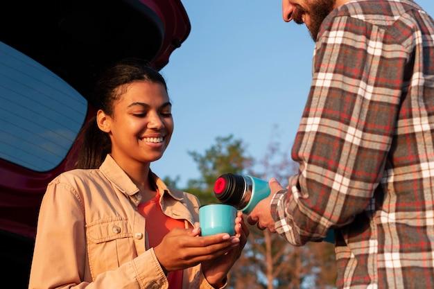 Mężczyzna nalewa kawę dla swojej dziewczyny