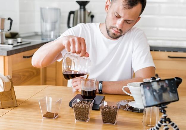 Mężczyzna nalewa kawę w filiżance