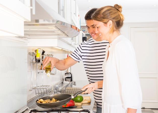 Mężczyzna nalewa oliwa z oliwek w kulinarnych warzywach w smaży niecce