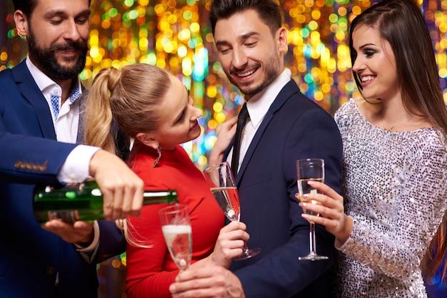 Mężczyzna nalewa szampana swoim przyjaciołom