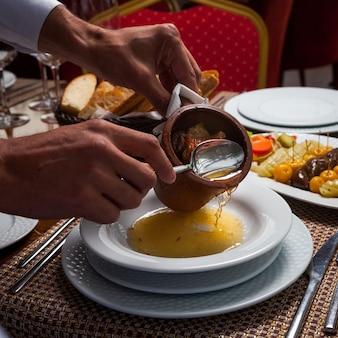 Mężczyzna nalewa wyśmienicie wschodniego grochową zupę z mięsem w talerz na drewnianym stole. wysoki kąt widzenia.
