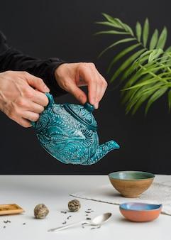Mężczyzna nalewania herbaty w miski
