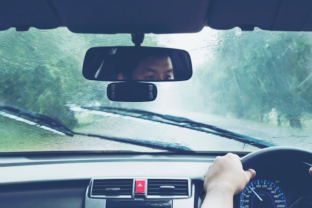 Mężczyzna napędowy samochód w ciężkich opadach deszczu