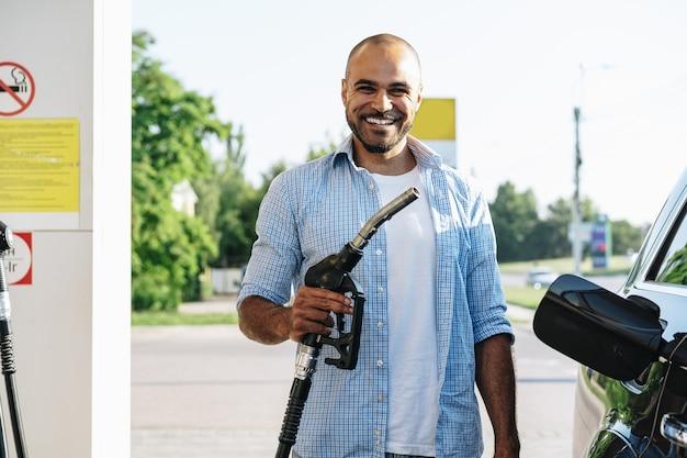 Mężczyzna napełniający paliwo benzynowe w samochodzie na stacji benzynowej